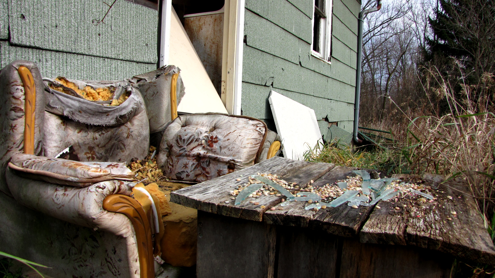 Broken chair in front of abandoned house